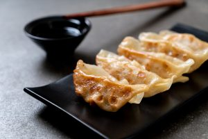 gyoza dumplings on a black slim plate next to soy sauce