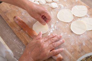 hands and rolling pin rolling dumpling dough